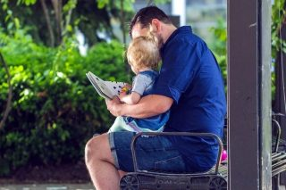 A child sitting on a man's lap being read a story outside on a bench.
