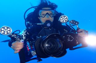 Ayisha holding an underwater camera and SCUBA diving in the ocean