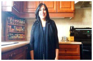 Ayisha standing in her kitchen