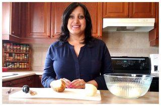 Ayisha peeling potatoes in her kitchen