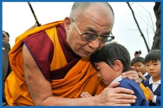 Dalai Lama and a child who appears to be sad, embracing