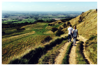 2 people walking along a path on a hillside