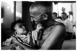 A baby and a smiling Mahatma Gandhi looking at each other